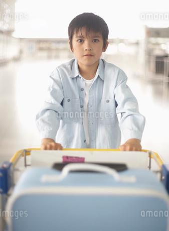 荷物の乗ったカートを押す男の子の写真素材 [FYI01890887]
