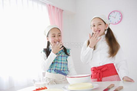 クリームの味見をする二人の少女の写真素材 [FYI01891108]