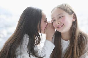 内緒話をして微笑む二人の少女の写真素材 [FYI01891218]