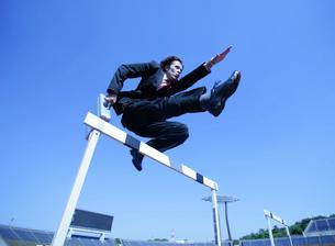 ハードルを飛び越えるビジネスマンの写真素材 [FYI01891280]