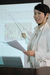 スクリーンを指し示しながら話す女性の写真素材 [FYI01891406]