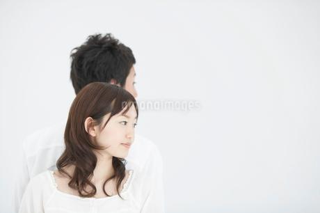 背中合わせの日本人の若者カップルの写真素材 [FYI01891729]
