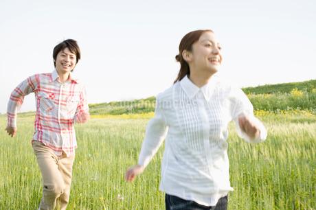 草むらを駆けるカップルの写真素材 [FYI01891739]