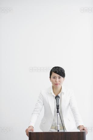 演台に両手をつきマイクに向かう女性の写真素材 [FYI01891747]