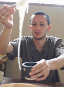 麺をすくう男性の写真素材 [FYI01891754]