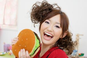 ハンバーガーのクッションを持つ女性の写真素材 [FYI01891884]