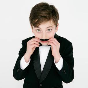 付け髭をするタキシードを着た男の子の写真素材 [FYI01892690]