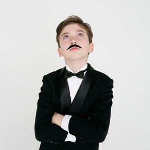 付け髭をするタキシードを着た男の子の写真素材 [FYI01893040]