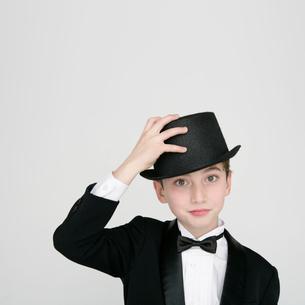 タキシードを着て帽子に手を当てる男の子の写真素材 [FYI01893047]