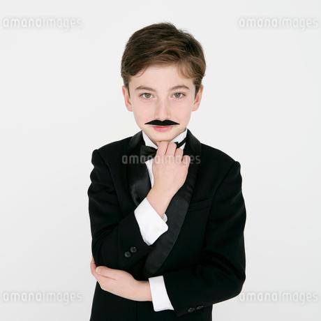 付け髭をするタキシードを着た男の子の写真素材 [FYI01893463]