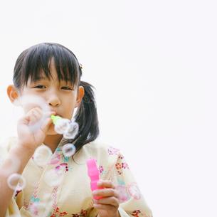 シャボン玉を吹く女の子の写真素材 [FYI01893728]