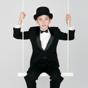 ブランコに乗るタキシードを着た男の子の写真素材 [FYI01893736]