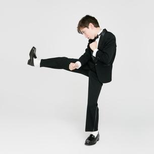 キックするタキシードを着た男の子の写真素材 [FYI01893806]
