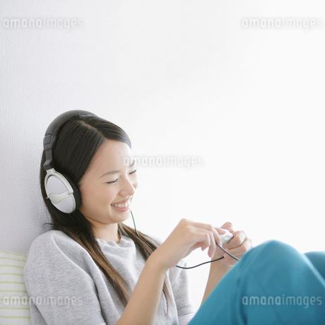 ヘッドホンで音楽を聴く女性の写真素材 [FYI01893840]