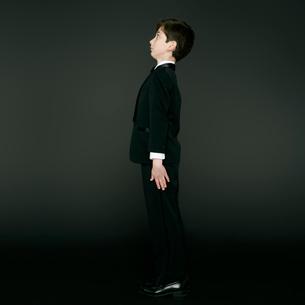 姿勢を正して立つタキシードを着た男の子の写真素材 [FYI01893922]