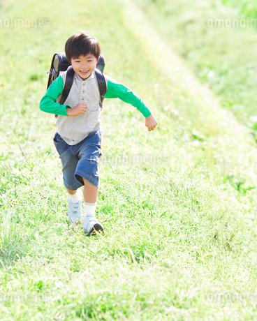 草原を走る小学生の写真素材 [FYI01895559]