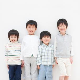 壁際に立って笑う男の子の写真素材 [FYI01895587]