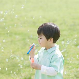 シャボン玉で遊ぶ男の子の写真素材 [FYI01896238]