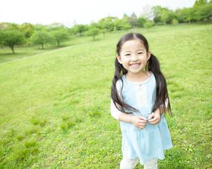 草原で笑う女の子の写真素材 [FYI01896864]