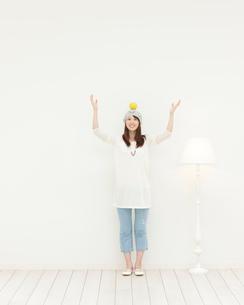オレンジを頭の上にのせて立つ女性の写真素材 [FYI01897133]
