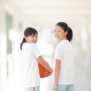 バスケットボールを持って振り返る二人の女の子の写真素材 [FYI01897150]