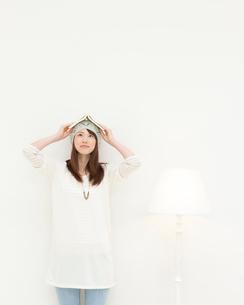 本を頭の上にのせて見上げる女性の写真素材 [FYI01897366]