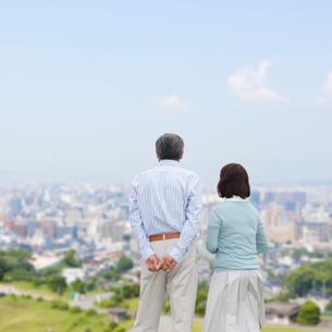 遠くを眺めるシニア夫婦の後ろ姿の写真素材 [FYI01898200]