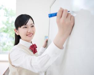 ホワイトボードに向かう女子高生の写真素材 [FYI01898229]