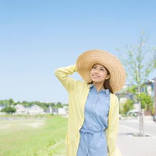 帽子をおさえて見上げる女性の写真素材 [FYI01898821]