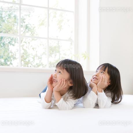寝転んで頬杖をつく2人の女の子の写真素材 [FYI01899211]