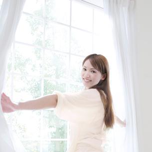 カーテンを開けて振り向く女性の写真素材 [FYI01899632]