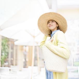 帽子をおさえて遠くを見る女性の写真素材 [FYI01899743]