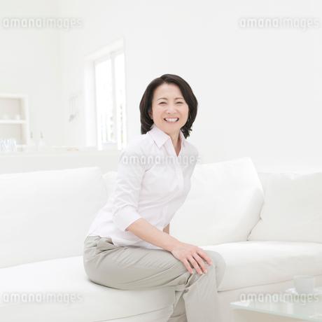 ソファに座って笑顔の女性の写真素材 [FYI01899967]