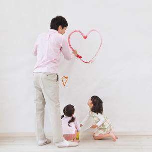 壁に落書きをする親子の後ろ姿の写真素材 [FYI01900176]