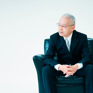 椅子に座って手を組むビジネスマンの写真素材 [FYI01900380]