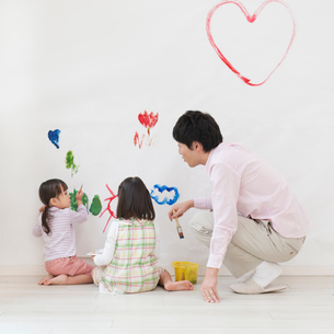 壁に落書きをする親子の写真素材 [FYI01900406]