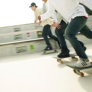 スケートボードに乗る3人の男性の写真素材 [FYI01901607]