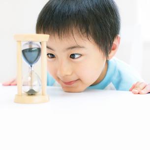 砂時計を見る男の子の写真素材 [FYI01901697]