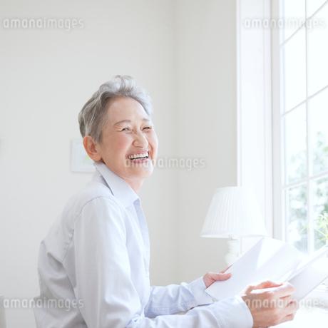 窓辺に座る日本人シニア女性の写真素材 [FYI01901825]