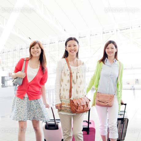 キャリーバッグを持って歩く女性達の写真素材 [FYI01902118]
