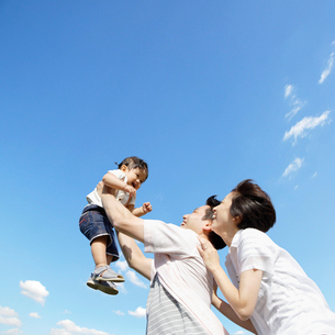 娘を抱きあげてあやす両親の写真素材 [FYI01902265]