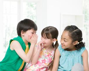 内緒話をする3人の子供の写真素材 [FYI01902268]