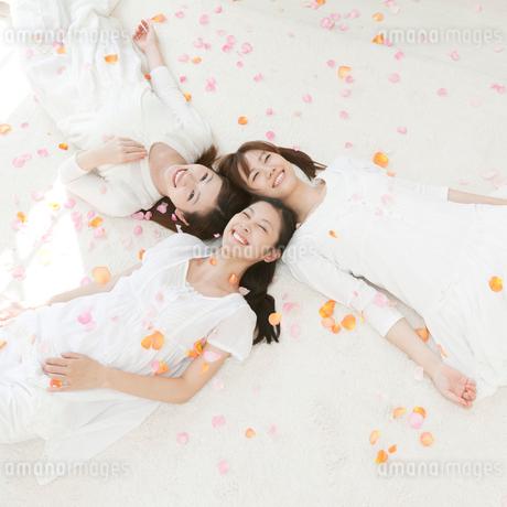 花弁と笑顔で寝転ぶ女性達の写真素材 [FYI01902297]
