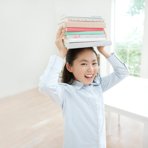 本を頭に乗せた日本人の女の子の写真素材 [FYI01902756]