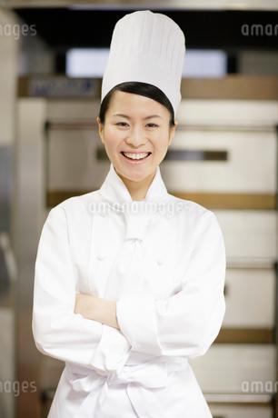 腕を組んで正面を見つめる笑顔の女性の写真素材 [FYI01902888]