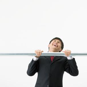 鉄棒にぶら下がるビジネスマンの写真素材 [FYI01903475]