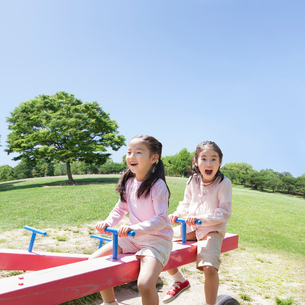 シーソーで遊ぶ日本人姉妹の写真素材 [FYI01903969]