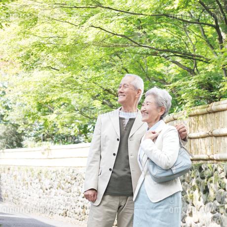 石垣の塀の前に立つシニア夫妻の写真素材 [FYI01904032]
