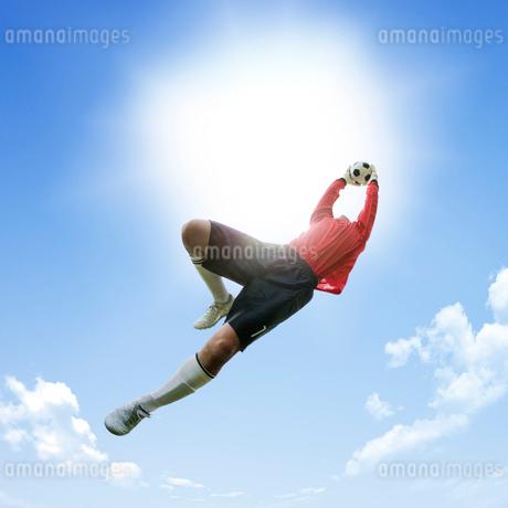 青空とサッカーボールをつかむゴールキーパーの写真素材 [FYI01904262]