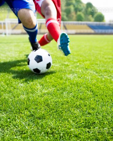 ボールを取り合う2人の選手の足元の写真素材 [FYI01904822]